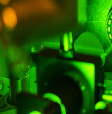 Green laser light shines on metal lab tools.