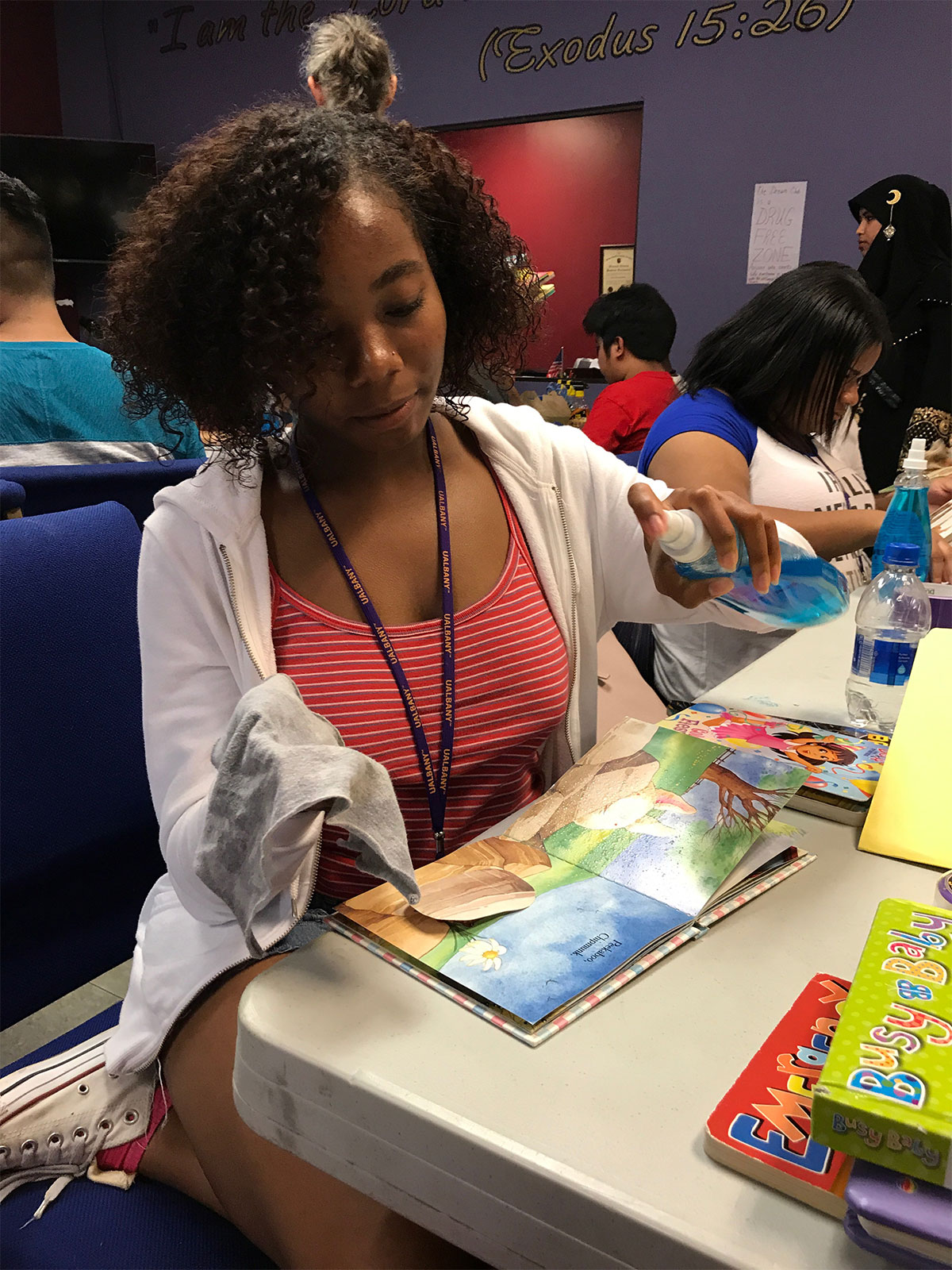An african-american female UAlbany EOP student cleans childrens books at a table.