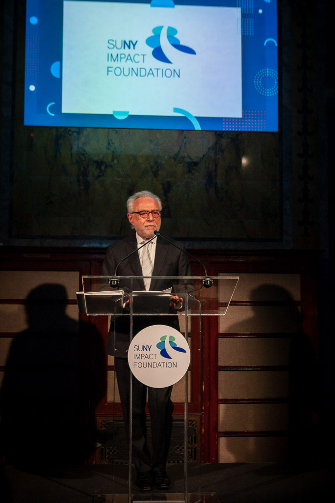 Wolf Blitzer speaks at a podium at the SUNY Impact Foundation Chancellor inauguration gala.