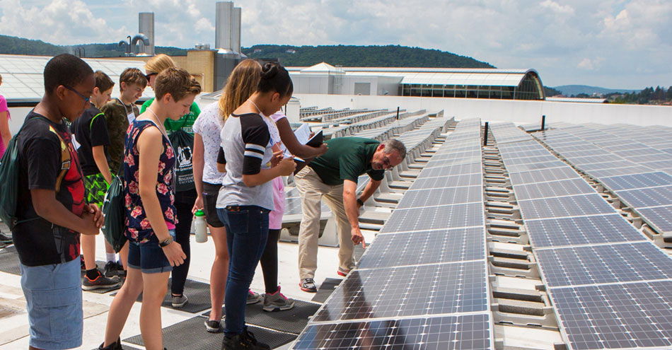 Binghamton University professor shows students a solar panel setup on a rooftop.