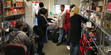 Students look through items on shelves in a campus food bank.