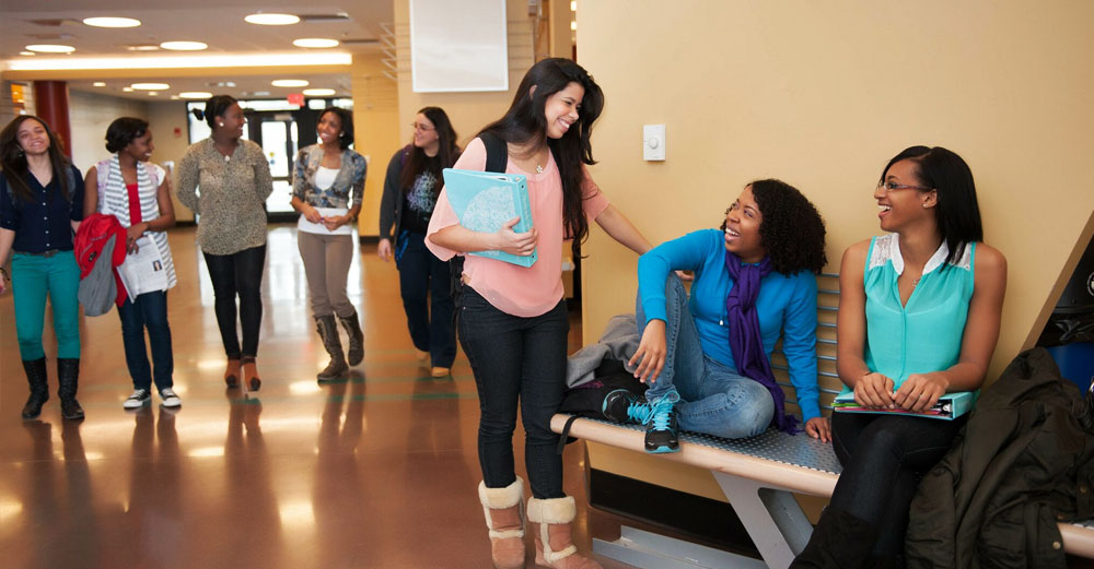 Groups of diverse students mingle in a hallway at Farmingdale State College.