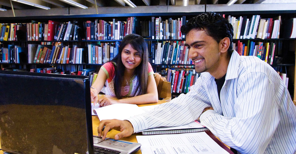 A male and female student review something on a laptop in the HVCC library.