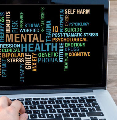 Laptop with mental health phrases on screen.