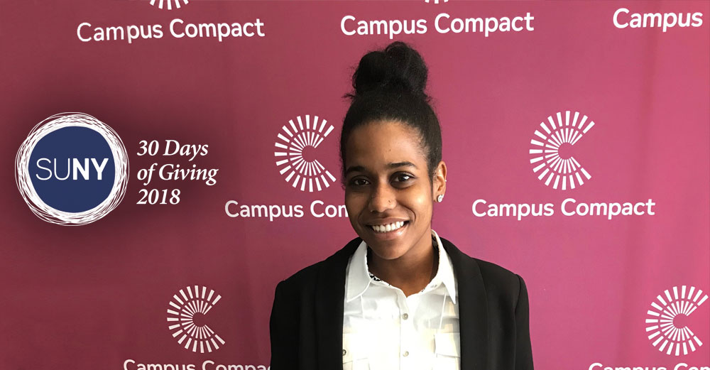 Buffalo State student Ada Boston in front of Campus Compact banner.