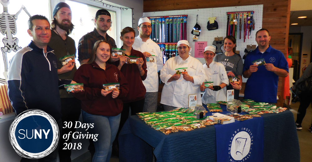 Niagara County Community College culinary students behind a table of pet treats they created.
