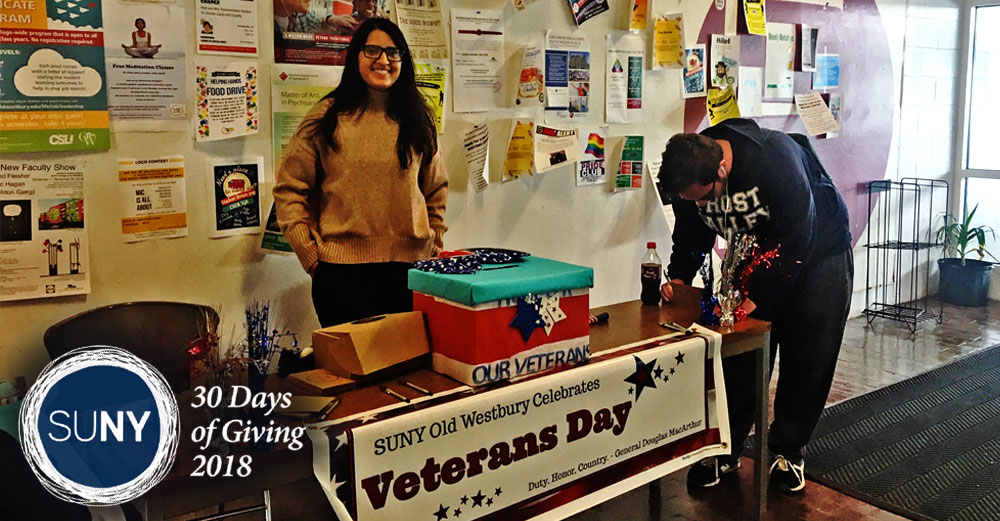 SUNY Old Westbury students stand at a table with letters offering letters to be written to send to veterans.