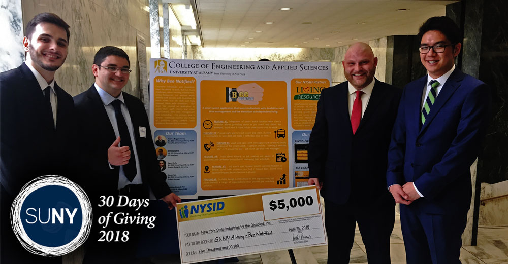 4 UAlbany College of Engineering and Applied Sciences students in suits stand in front of sign showcasing their BEE-notified project.