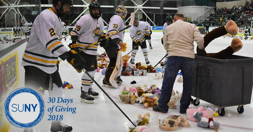 SUNY Oswego hockey players help clean teddy bears off the ice during a game.