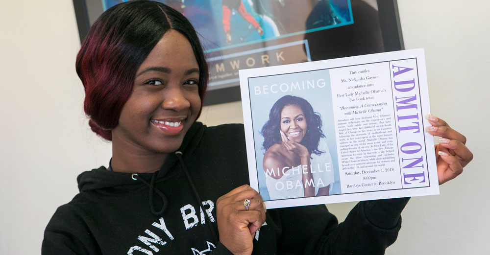 African American female student from Stony Brook holds an 'admit one' ticket to Michelle Obama's book tour.