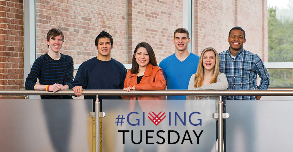 Students line up behind a short railing with Giving Tuesday laying in front of it.