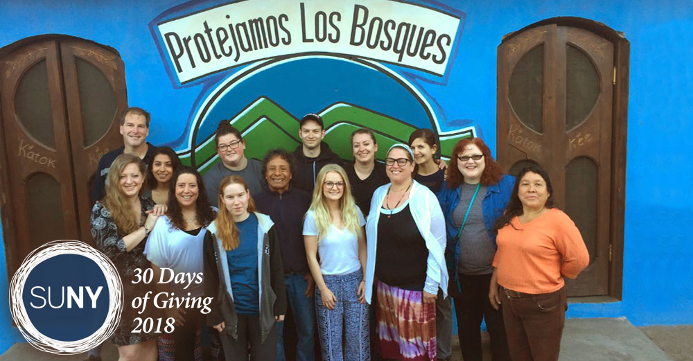 Onondaga Community College students stand together in fron of a building in Guatemala.