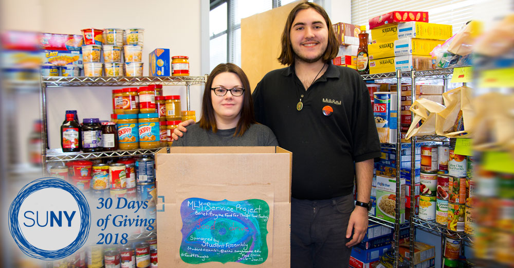 A male and female SUNY Broome student stand inside a food pantry with loaded shelves of food stuff.