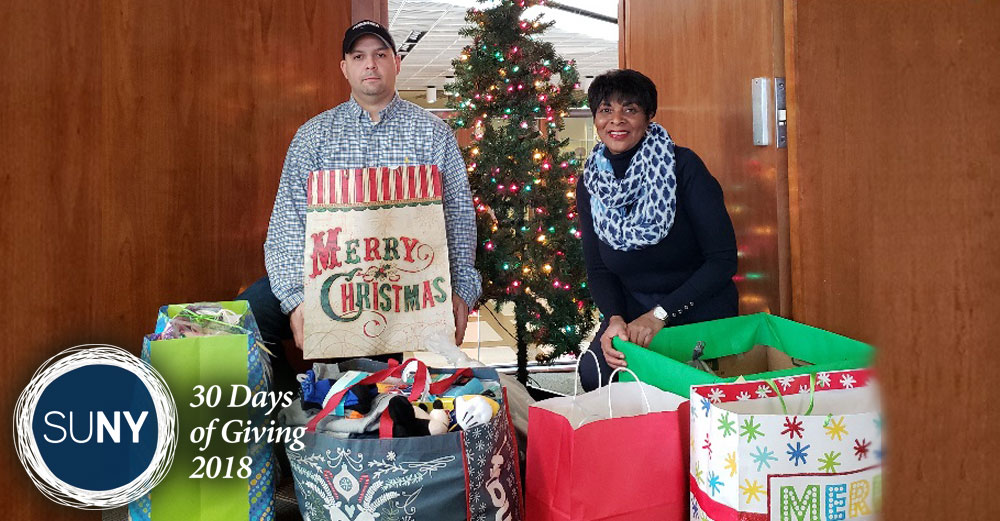 Two SUNY Fredonia staffers stand behind bags full of Christmas gifts.