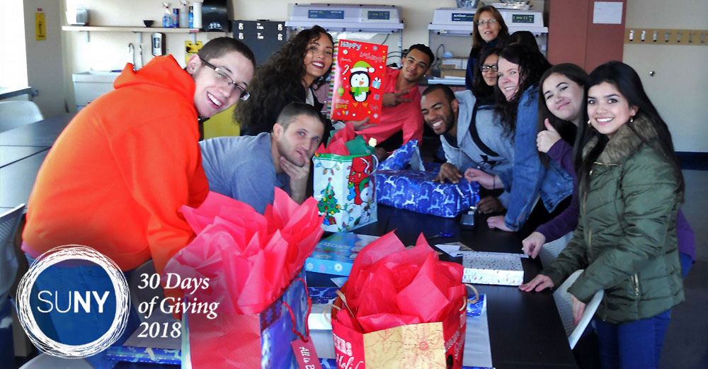 SUNY Orange students package blankets and jackets into boxes covered in christmas gift wrapping for donation.