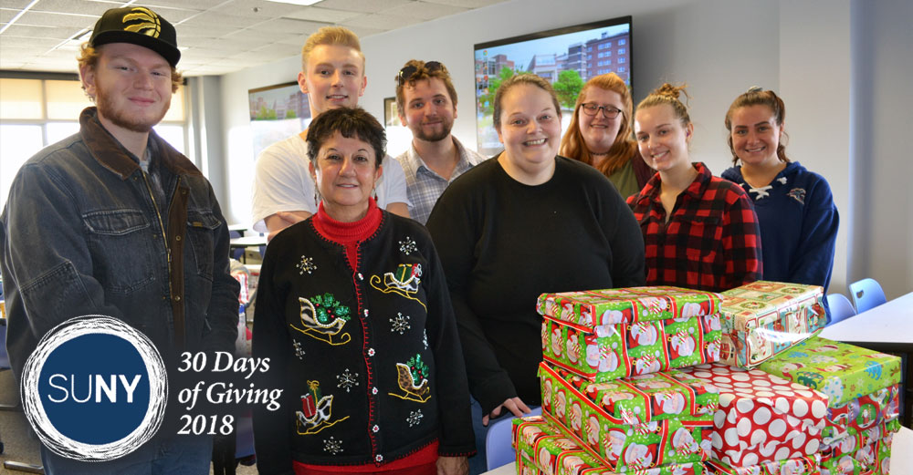 Schenectady County Community College students and staff at a table that has piles of wrapped presents.