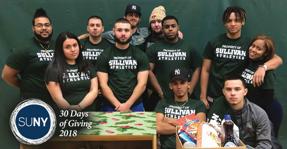 SUNY Sullivan students at a table with boxes of food donations on it.