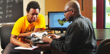 African-American engineering student sits with professor looking over model car.