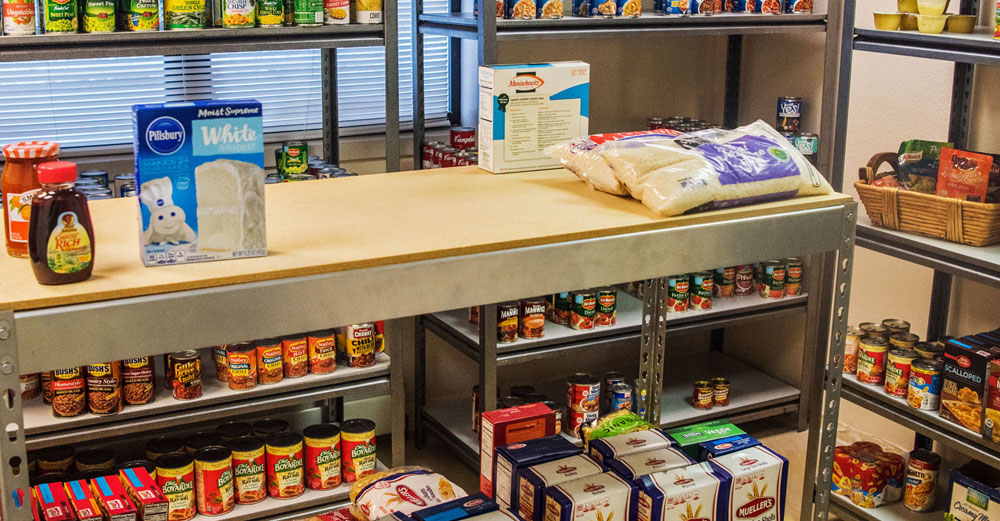 A food pantry with lots of non-perishable food stuff on the shelves.