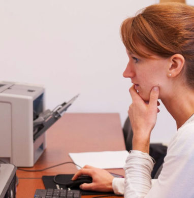 Red haired female student sits at a computer reading a website.