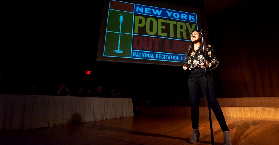 A girl stands on a wooden stage behind a microphone during a Poetry Out Loud competition.