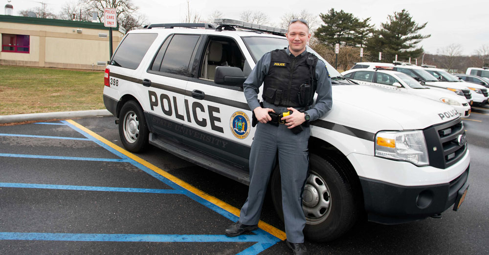 Lt. Zachary Lee of the Farmingdale State College University Police stands against his squad SUV outside.