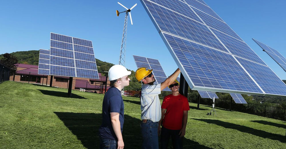 Students and teacher examine a large solar panel in the ground at SUNY delhi.