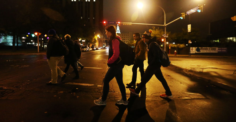 Students crossing a street at a large intersection at night.