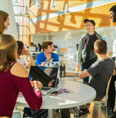 Students sit and talk at tables of a University at Buffalo student lounge.