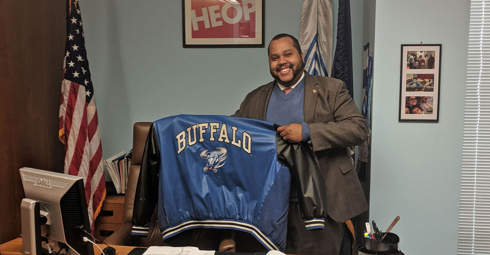NYS Assemblyman Victor Pichardo in his office holding up his old UBuffalo jacket.