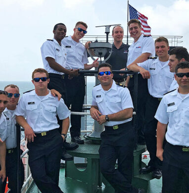 Maritime College cadets stand outside on the deck of the Empire State VI training ship during the summer at sea 2019.