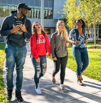 Diverse group of students walk outside on the SUNY Cortland campus.