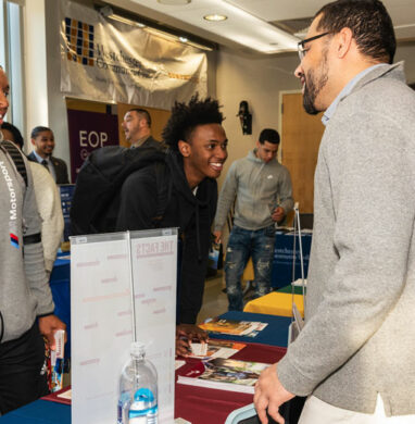 Event table at Westchester Community College with minority students talking to college representatives.