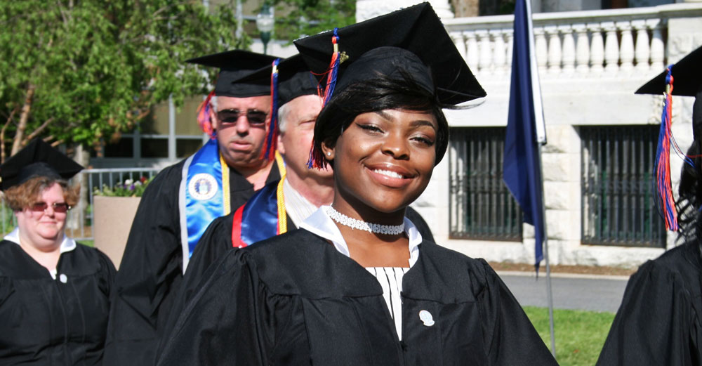 African-american female graduate in cap and gown.