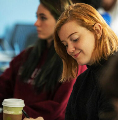 Girl student at SUNY Purchase smiles at her desk in a classroom.