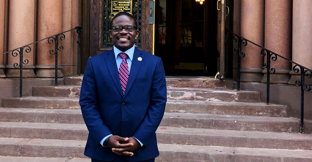 Albany city councilman Owusu Anane stands in front of city hall.