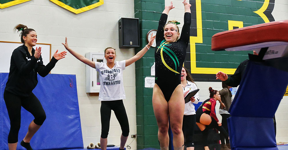 A member of the College at Brockport womens gymnastics team smiles at the end of her vault routine.