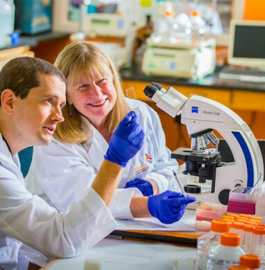 Dr. Rittenhouse-Olson with senior scientist John Fisk, looking at a microarray slide with JAA-F11 tumor staining.