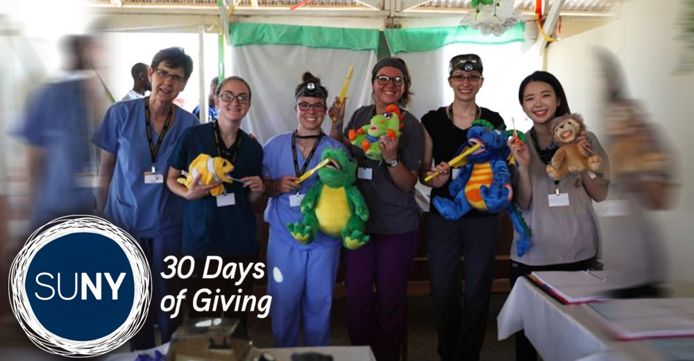 SUNY Broome dental students pose with stuffed animals in a medical tent.