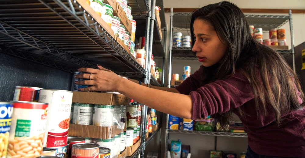 SUNY New Paltz graduate student Mandy Maldonado '16 (Latin American & Caribbean Studies / Spanish) '18g (Humanistic-Multicultural Education) reaches for food items in New Paltz campus food pantry.
