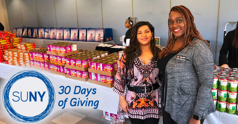 2 female Westchester Community College students stand in front of a large table of donated food items.
