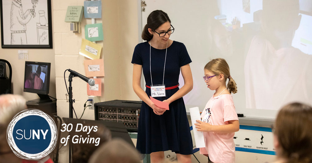 Female teacher stands next to elementary school student as she speaks in front of her class.