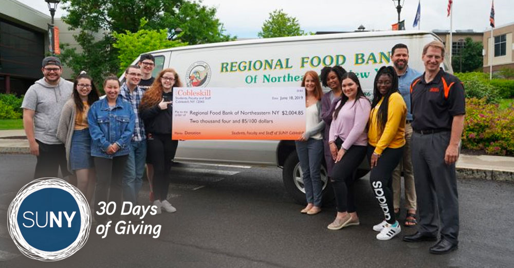 SUNY Cobleskill students and staff stand with a giant check in front of Regional Food Bank van.