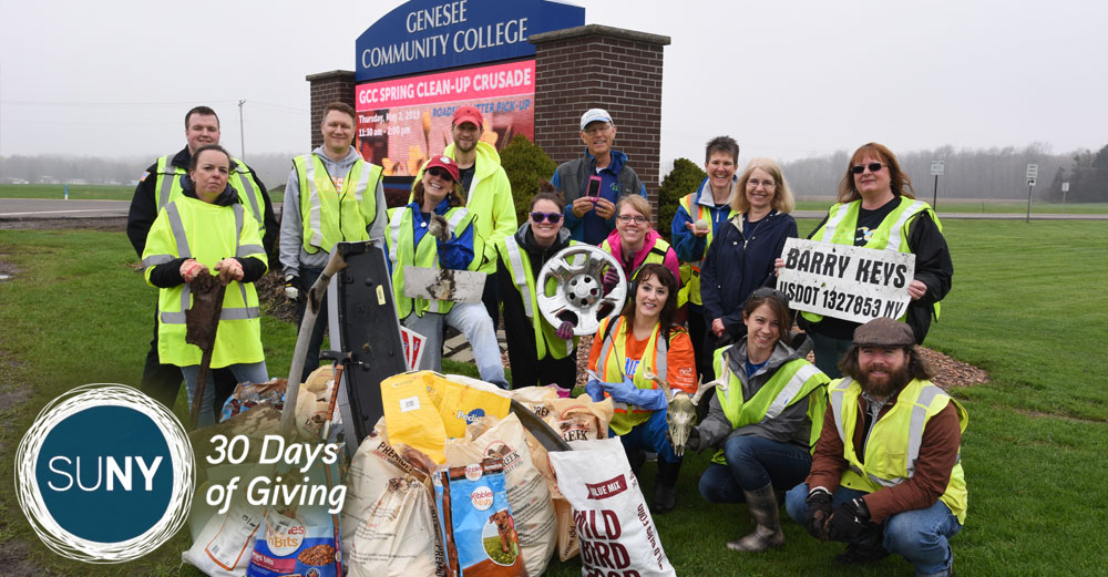 Group of people in front of Genesee Community College sign after doing grounds cleanup.