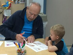 A toddler colors with an elderly man.