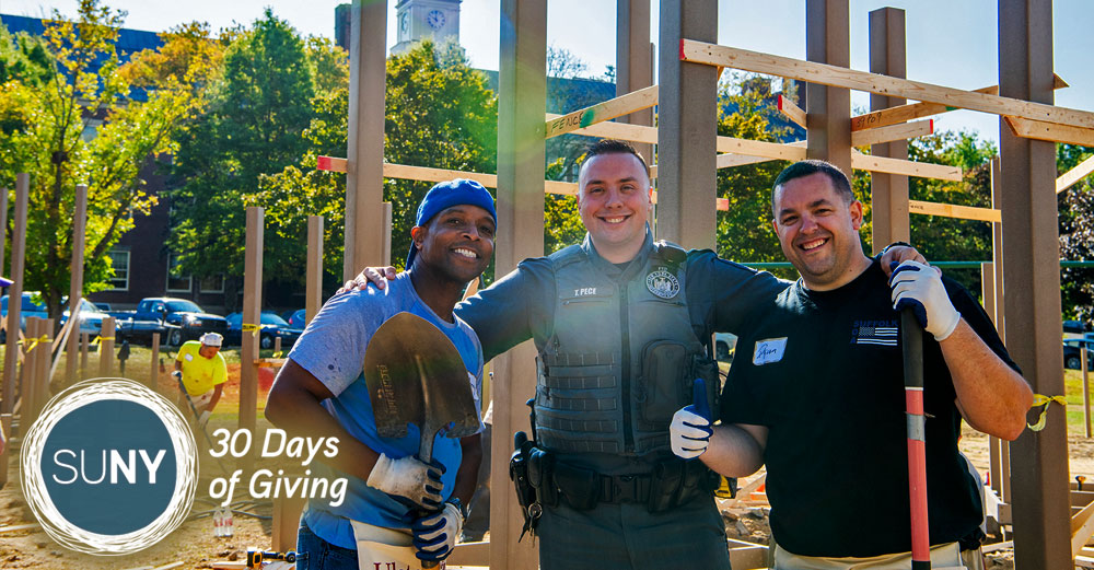 New Paltz student and staff member with a university police officer at a build site for a playground.