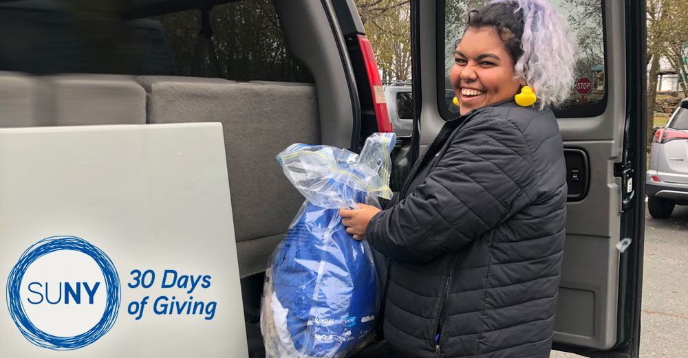 SUNY Purchase College student loads clothing donations into van.
