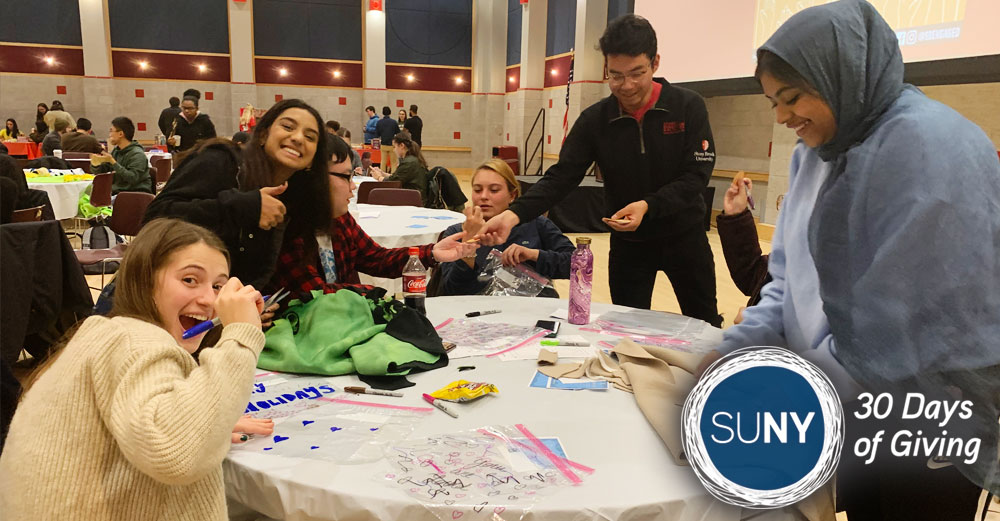 Stony Brook University students smiling and waving while seated at a table full of art supplies in gym.