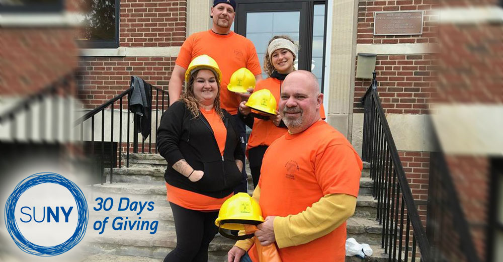 Jamestown Community College students and staff in vests and hard hats outide a brick building.