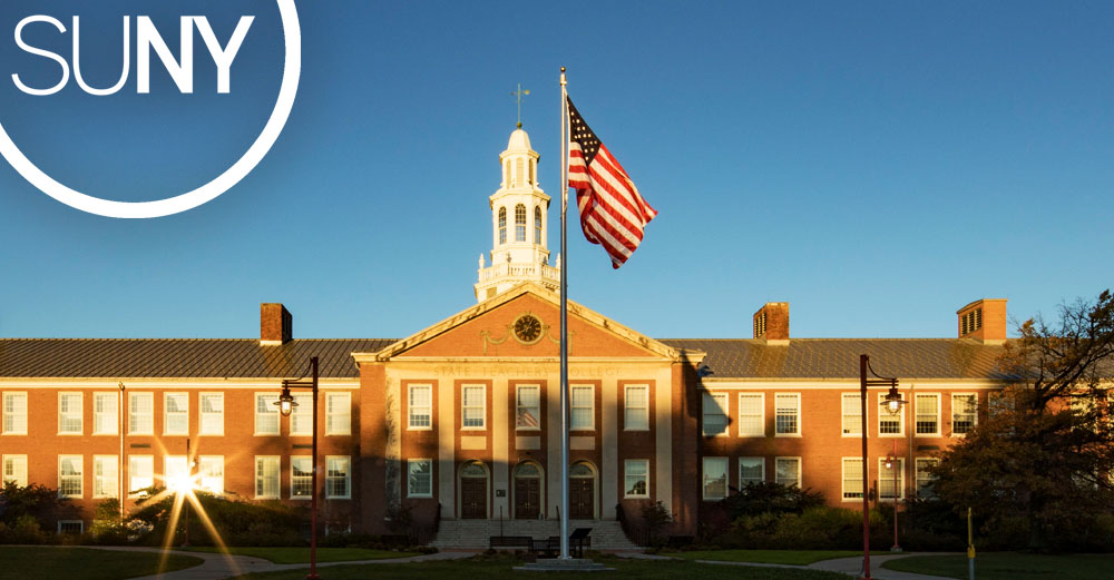 SUNY College at Brockport Hartwell Hall exterior with American Flag in front.